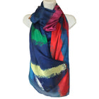 Ladies long scarf background colour is blue with reds, yellow, orange, fucsia, green