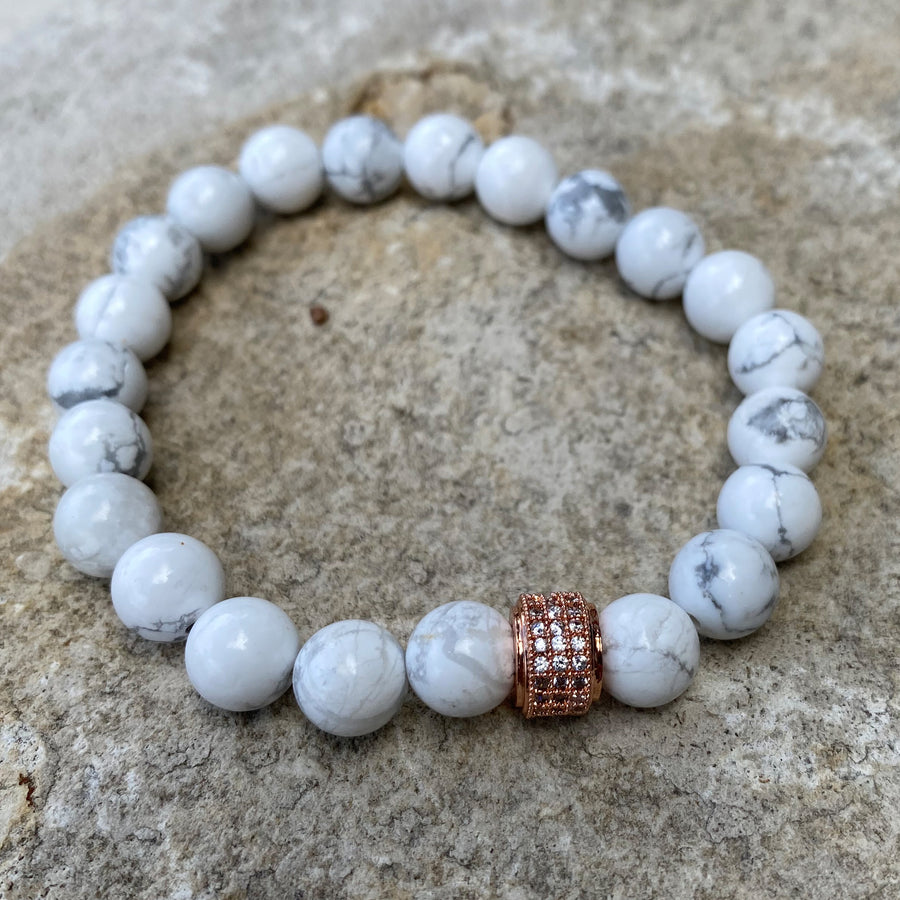 Gemstone bracelet with white stones and a rose gold crystal charm