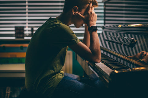 Young man struggling with piano practice