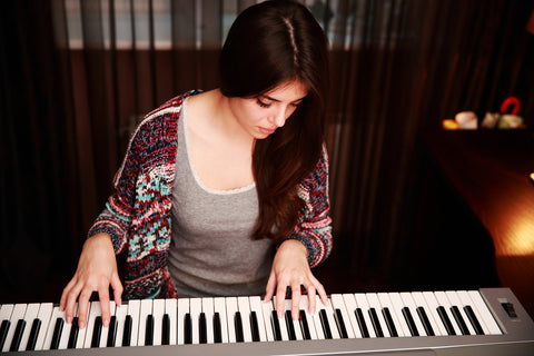 young white woman looking at piano keys and hand carefully