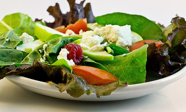a plate of salad with some cheese