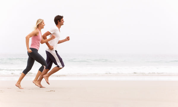 woman and man jogging by the shore
