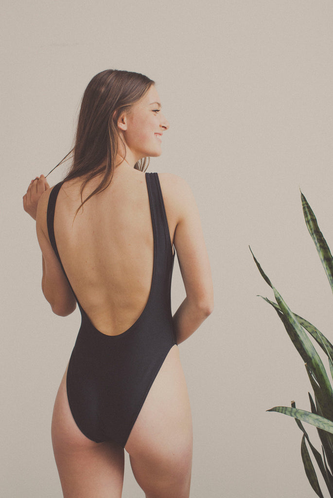 high cut leg swimsuit in black with prsvnt text