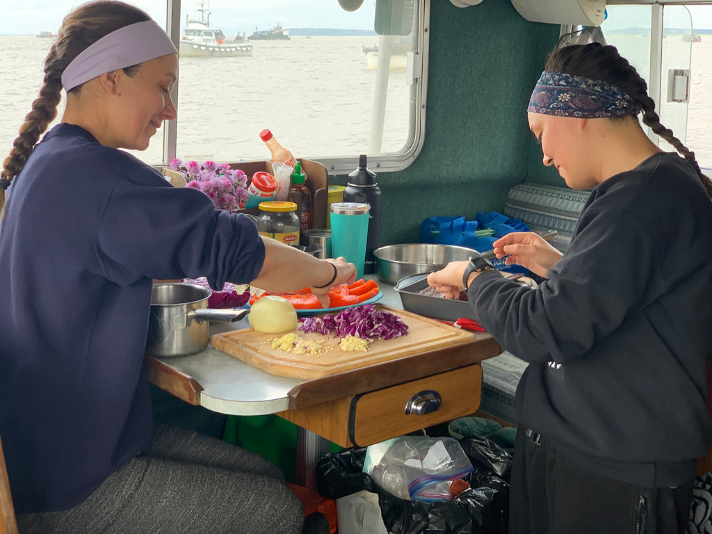 Ashley and Nora prepare a sockeye lunch while anchored up, waiting for the fishery-opening announcement.