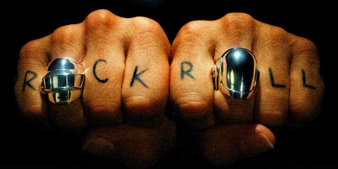 SHOT OF 2 FISTS WITH ROCK AND ROLL TATTOOED ON THE FINGERS WEARING THE DAFT PUNK GUY AND THOMAS RINGS IN SILVER