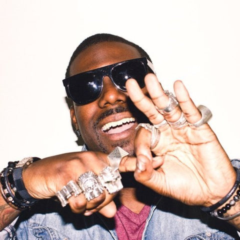 KING CHIP POSING ON A WHITE BACKGROUND WITH HIS HAND ON HIS FOREHEAD WITH HIS HANDS MAKING A GESTURE AND BOTH HANDS COVERED IN STERLING SILVER HAN CHOLO RINGS