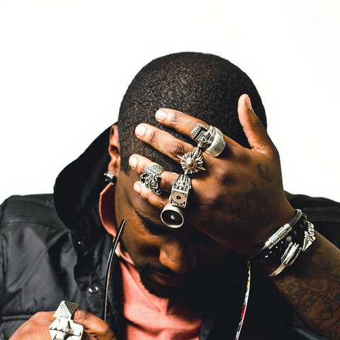 KING CHIP POSING ON A WHITE BACKGROUND WITH HIS HAND ON HIS FOREHEAD WITH HIS HAND COVERED IN STERLING SILVER HAN CHOLO RINGS