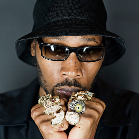RZA OF THE WU TANG CLAN WEARING BLACK SUNGLASSES AND A BLACK HAT CLINCHING HIS FISTS CLOSE TO HIS FACE WHILE ROCKING SEVERAL 14K GOLD HAN CHOLO RINGS