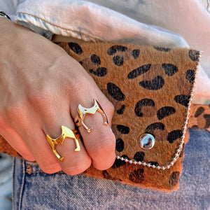 shot of a woman wearing the catra ring in gold and silver from the she-ra collection