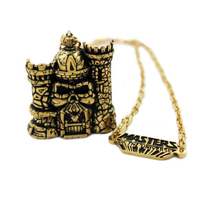 front of the castle grayskull pendant in gold from the masters of the universe collection