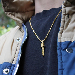 photo of a man in a vintage jacket showing the gold green ranger dragon dagger pendant on a chain
