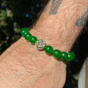 green aventurine power rangers bead bracelet worn by a man with tattoos in the sun
