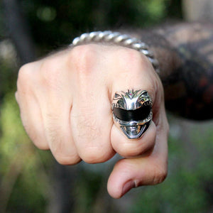 shot of the green ranger ring on the pointer finger of a man with a fist with plants in the back