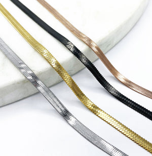 shot of the of the gunmetal, silver, gold and rose gold herring bone chains side by side on marble