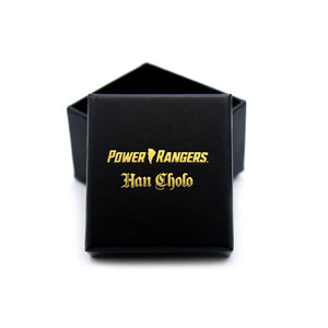 shot of the mighty morphin power rangers black a gold foil ring box on a white surface