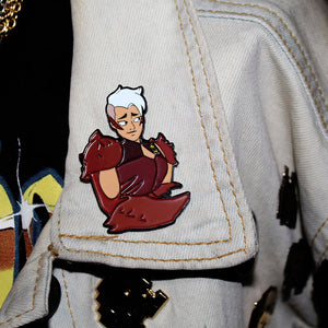 shot of the scorpia enamel pin on a grey jean jacket collar with other pins on the jacket