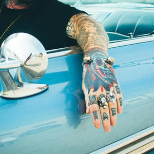 shot of a man in a lowrider wearing the Brain Dead cuff from the han cholo skulls collection