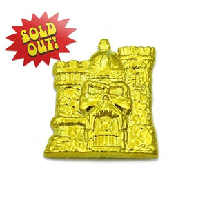 front of the 3D gold castle grayskull pin from the masters of the universe jewelry collection