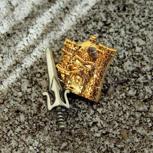 shot of the 3D gold castle grayskull and power sword pin on a gravel and rock surface