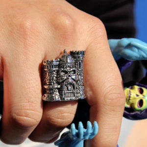 shot of the Castle grayskull ring on a mans hand holding a vintage skeletor toy