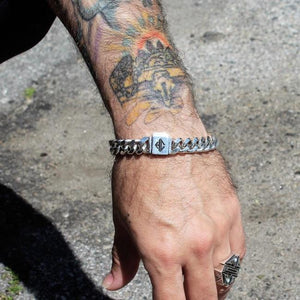 shot of a man with tattoos wearing the classified chain bracelet