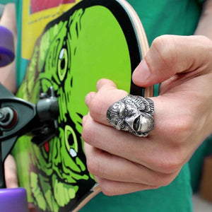 man wearing the Creature From The Black Lagoon Ring holding a creature skate deck