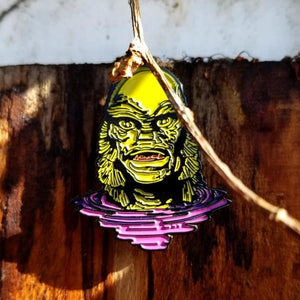 shot of the creature lurking enamel pin on a wooden background