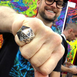 shot of the artist skinner wearing a silver d20 ring with his artwork displayed in the background
