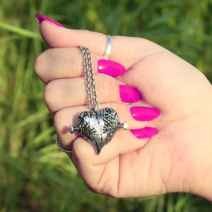shot of a woman wearing pink nail polish holding the silver frankenheart pendant in her hand