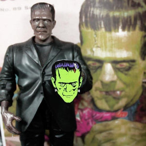 shot of a frankenstein toy holding the frankenstein pin with a frankenstein illustration behind it