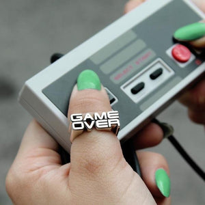 shot of a girl playing with a nintendo DS controller wearing the game over ring
