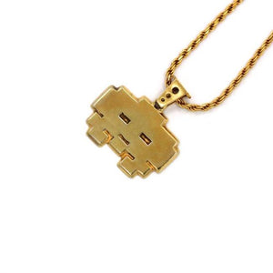 right angle view of the grumpy invader pendant in gold on a white background