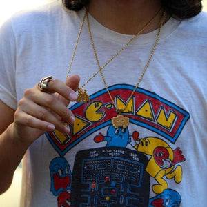 shot of a man wearing a vintage pac man t shirt holding up the grumpy invader pendant in gold