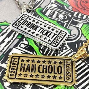 shot of the drink ticket pendant in gold and silver on the hc roses graphic t shirt