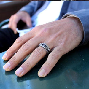 shot of a man wearing the his till death do us part ring on his hand on a green table