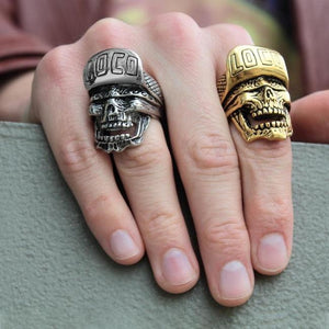 shot of a man wearing the loco skull ring in gold and one in silver