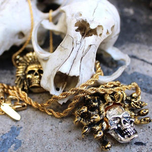 shot of the medusa skull pendant and other gold rings with an animal skull