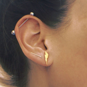 front view of the Mighty Morphin Power Rangers Bolt Earrings in gold on a woman with ear piercings