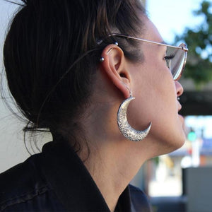 shot of a woman wearing the moon earrings in silver from the han cholo fantasy collection