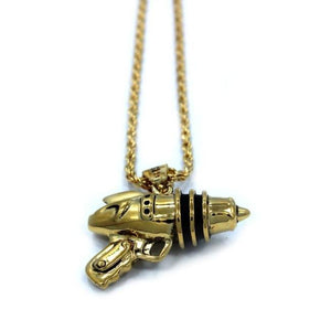 left up close shot of the Ray Gun Pendant in gold on a white surface