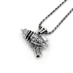 right angled shot of the Ray Gun Pendant in silver on a white surface
