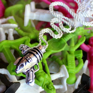 shot fo the ray gun pendant in silver on a colorful alien background
