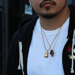 shot of a man wearing the first of fury and robot pendant in gold in a white shirt and black hoodie
