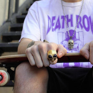 shot of a man wearing the roswell ring in gold and a deathrow records t shirt
