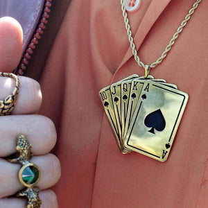 shot of a man in an orange shirt wearing the royal flush pendand with gold rings on