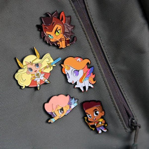 picture of all 5 she-ra chibi enamel pins pinned to a backpack right next to a zipper