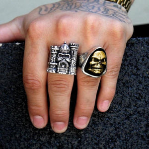 shot of the skeletor and castle grayskull ring on a mans hand holding a black brick