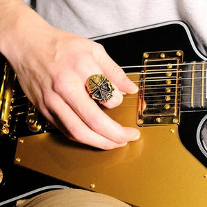 shot of a man playing guitar and wearing the Skull Ring in gold from the fantasy collection