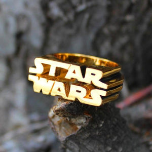 shot of the Star Wars Logo Ring in gold on a grey background from the star wars collection