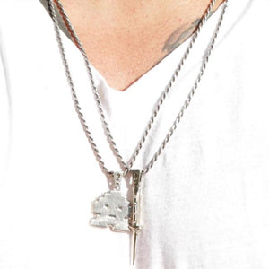 shot of a man wearing the switchblade and stoney invader pendants in silver in a white shirt
